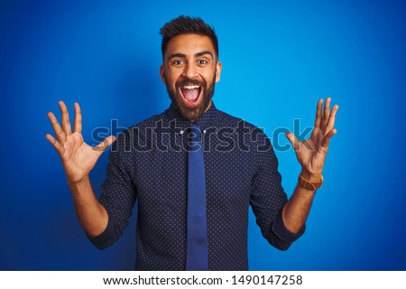 Young indian businessman wearing elegant shirt and tie standing over isolated blue background celebrating crazy and amazed for success with arms raised and open eyes screaming excited. Winner concept