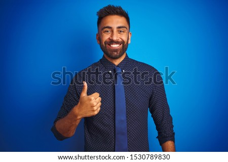 Young indian businessman wearing elegant shirt and tie standing over isolated blue background doing happy thumbs up gesture with hand. Approving expression looking at the camera showing success.