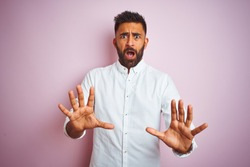 Young indian businessman wearing elegant shirt standing over isolated pink background afraid and terrified with fear expression stop gesture with hands, shouting in shock. Panic concept.