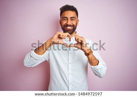 Young indian businessman wearing elegant shirt standing over isolated pink background smiling in love doing heart symbol shape with hands. Romantic concept.