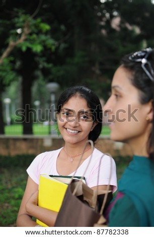 Young Indian College girl holding books in her hand.
