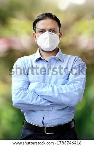 Young Indian confident businessman in mask standing outdoors. Corona warrior at work in India. Corona warriors doing work amid risk of Covid-19 pandemic. Helping the economy. Economy warriors.
