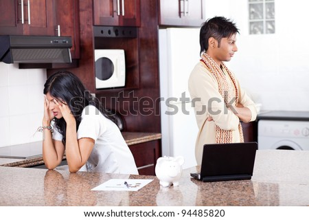 young indian couple arguing on money in home kitchen