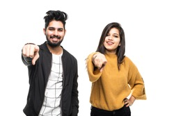 Young indian couple in love in camera pointing at you with index fingers isolated over white background.