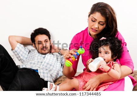 young Indian couple relaxing and enjoying with their daughter
