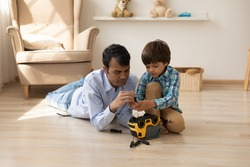 Young indian daddy and preschooler son work on heated floor at living room focused on repairing toy car. Caring hindu foster dad help little adopted boy to fix plastic truck teach to use screwdriver