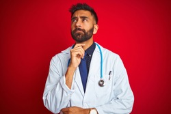 Young indian doctor man wearing stethoscope standing over isolated red background with hand on chin thinking about question, pensive expression. Smiling with thoughtful face. Doubt concept.