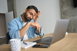 Young indian eastern tired exhausted business man rubbing eyes sitting in modern home office with laptop on desk. Overworked burnout academic Hispanic student with glasses in hand feeling eyestrain.