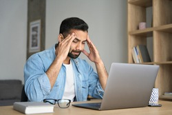 Young indian exhausted business man massaging temples suffering from headache in modern home office with laptop on desk. Overworked burnout academic Hispanic student feeling migraine head strain.