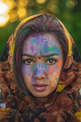 Young Indian faces in paint. A woman in traditional Indian dress celebrates Holi by color festival. A girl with black hair with a scarf on her head. Brown eyes oriental girls