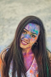Young Indian faces in paint. Woman in dress celebrates Holi festival. Girl with black hair. Brown eyes oriental girls. Smiling girl