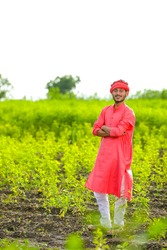 Young indian farmer standing in green pigeon pea field