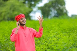 Young indian farmer talking on mobile phone at green pigeon field