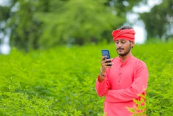 Young indian farmer using smartphone at green field