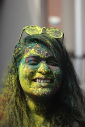 Young Indian girl celebrating the festival of Holi with yellow, red, green colours on her face. young indian girl wearing glasses celebrating holi festival