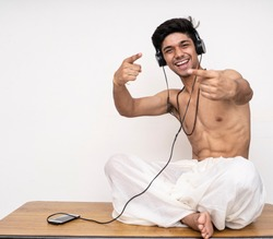 Young indian handsome boy wearing dhoti,listening to songs on his headphones, cheerful and happy.