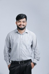Young Indian Handsome man standing over white background