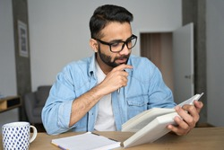 Young indian latin eastern male student in glasses reading book writing notes in textbook at home workplace. High school, university, college exams preparation. Remote distant education concept.