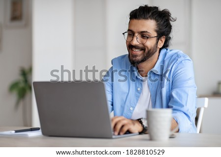Young Indian Male Writer Using Laptop Computer, Sitting At Desk In Home Office, Handsome Western Man In Eyeglasses Typing On Keyboard And Looking At Screen, Enjoying Working Remotely, Selective Focus