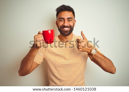 Young indian man drinking red cup of coffee standing over isolated white background happy with big smile doing ok sign, thumb up with fingers, excellent sign #1460121038