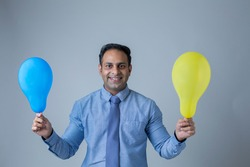 Young Indian Man Holding Air Balloons In His Hand.