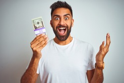Young indian man holding dollars standing over isolated white background very happy and excited, winner expression celebrating victory screaming with big smile and raised hands
