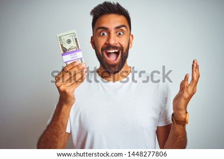 Young indian man holding dollars standing over isolated white background very happy and excited, winner expression celebrating victory screaming with big smile and raised hands #1448277806