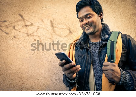 Young indian man holding mobile phone - Cheerful asian model next to old urban wall - Soft vintage filtered look focus on person face