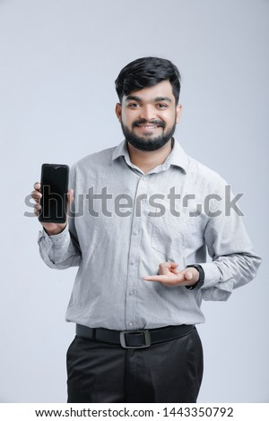 Young Indian man showing mobile screen #1443350792
