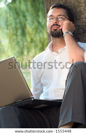 Young Indian man sitting by the tree with laptop and mobile phone.