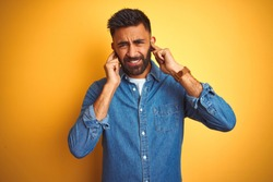 Young indian man wearing denim shirt standing over isolated yellow background covering ears with fingers with annoyed expression for the noise of loud music. Deaf concept.