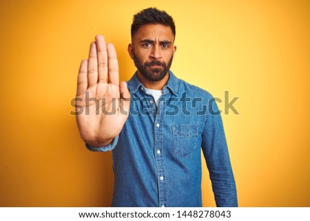 Young indian man wearing denim shirt standing over isolated yellow background doing stop sing with palm of the hand. Warning expression with negative and serious gesture on the face.