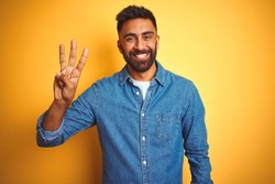 Young indian man wearing denim shirt standing over isolated yellow background showing and pointing up with fingers number three while smiling confident and happy.
