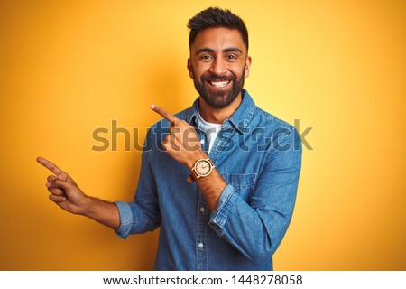 Young indian man wearing denim shirt standing over isolated yellow background smiling and looking at the camera pointing with two hands and fingers to the side.
