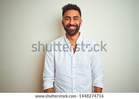Young indian man wearing elegant shirt standing over isolated white background with a happy and cool smile on face. Lucky person. #1448274716