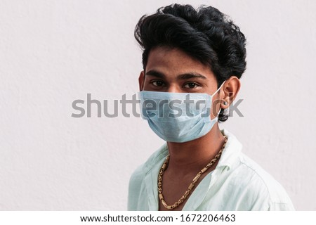 Young Indian man wearing mask to prevent himself from getting infection from Corona Virus pandemic