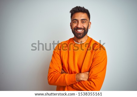 Young indian man wearing orange sweater over isolated white background happy face smiling with crossed arms looking at the camera. Positive person.