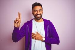 Young indian man wearing purple sweatshirt standing over isolated pink background smiling swearing with hand on chest and fingers up, making a loyalty promise oath