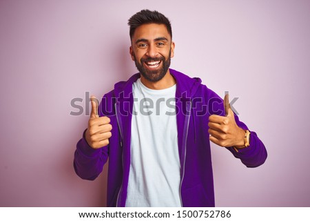 Young indian man wearing purple sweatshirt standing over isolated pink background success sign doing positive gesture with hand, thumbs up smiling and happy. Cheerful expression and winner gesture.