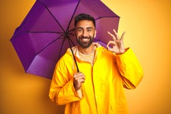 Young indian man wearing raincoat and purple umbrella over isolated yellow background doing ok sign with fingers, excellent symbol