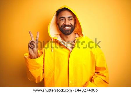 Young indian man wearing raincoat with hood standing over isolated yellow background smiling with happy face winking at the camera doing victory sign. Number two.