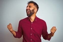 Young indian man wearing red elegant shirt standing over isolated grey background celebrating surprised and amazed for success with arms raised and eyes closed. Winner concept.