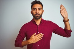 Young indian man wearing red elegant shirt standing over isolated grey background Swearing with hand on chest and open palm, making a loyalty promise oath