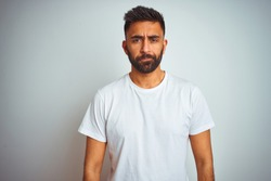 Young indian man wearing t-shirt standing over isolated white background depressed and worry for distress, crying angry and afraid. Sad expression.