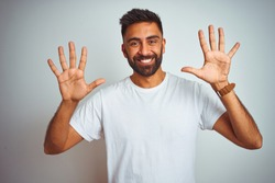 Young indian man wearing t-shirt standing over isolated white background showing and pointing up with fingers number ten while smiling confident and happy.