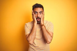 Young indian man wearing t-shirt standing over isolated yellow background afraid and shocked, surprise and amazed expression with hands on face