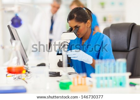young indian medical researcher looking through microscope in laboratory