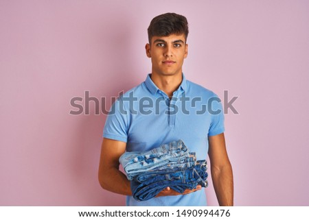 Young indian shopkeeper man holding folded jeans standing over isolated pink background with a confident expression on smart face thinking serious