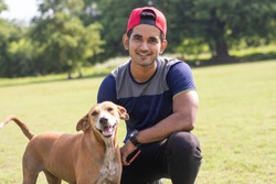 Young Indian sports man playing with dog in sports ground while jogging. Male  Sports and fitness concept.