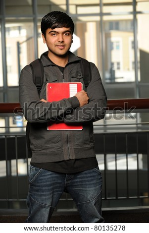 Young Indian student holding notebook